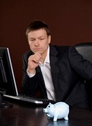 Businessman in deep thought, focus on piggy bank
