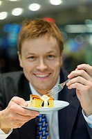 Businessman having a slice of cake