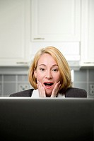Businesswoman surprised by information shown on her laptop