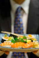 Businessman holding a plate of sushi