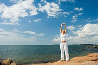 Woman practising yoga by the seaside