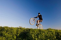 Man lifting the front wheel of bicycle while riding on it