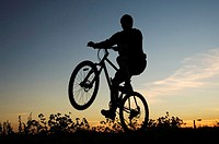 Silhouette of man lifting the front wheel of bicycle while riding on it
