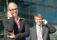 Businessman and businesswoman talking on the mobile phone