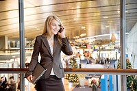 Businesswoman holding laptop while talking on mobile at airport terminal