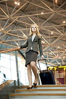 Businesswoman with luggage walking down the stairs at the airport terminal