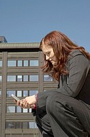 Businesswoman squatting down text messaging on the mobile phone