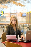 Businesswoman working in a cafe at the airport terminal