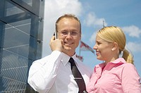 Businesswoman looking at businessman talking on the mobile phone
