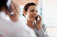 Businessman and Businesswoman Using Cell Phones
