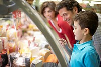 Family Looking at Fresh Cheese in Grocery Store