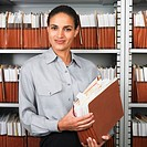 Hispanic businesswoman in file room