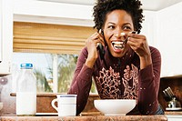 African American woman eating cereal (thumbnail)