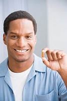 African American man holding up vitamin