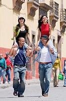 Hispanic women riding on boyfriend's shoulders