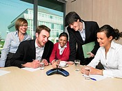 Happy Businesspeople Using Speakerphone in Meeting