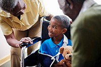 Senior Couple Talking to Young Boy in a Wheelchair