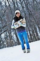 Asian woman carrying firewood in snow
