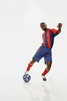 African American male soccer player kicking ball