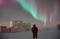 Aurora australis or southern lights display over a researcher at a research station in Antarctica  Auroral displays are caused by interactions between...