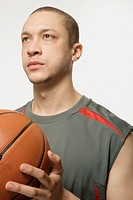 Mixed Race man holding basketball