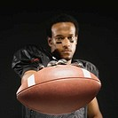 African American male football player holding out football