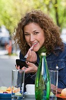 Hispanic woman applying lip gloss