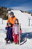 Asian mother and daughters in ski gear