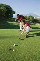 Multi-ethnic couple playing golf