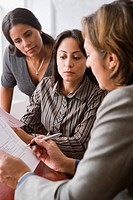 Hispanic businesswomen discussing paperwork