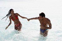 South American couple running in water