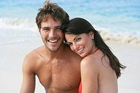 South American couple hugging on beach