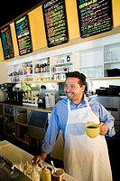Hispanic cafe owner holding coffee mug
