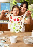 Hispanic mother and daughter making cookies