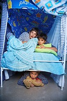 Hispanic boys hiding in bed fort