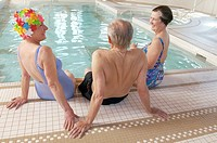 Three seniors sitting by swimming pool
