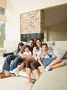 Hispanic family hugging on sofa