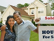 African American couple in front of new house (thumbnail)