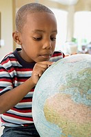 African American boy looking at globe