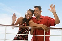 Hispanic couple waving at railing