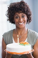 African American woman holding birthday cake
