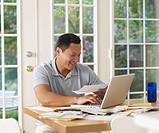 Asian man paying bills online
