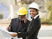 African American businesspeople with blueprints