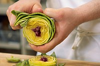 Cook peeling outer layers from an artichoke