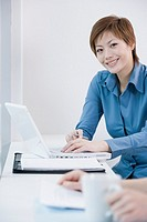 Asian businesswoman typing on laptop