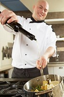 Chef adding olive oil to pan