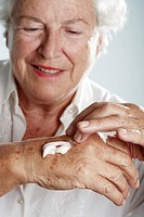Skincare  Elderly woman applying moisturising cream to the back of her hand