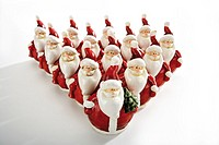 Santa claus figurines standig in form of a triangle