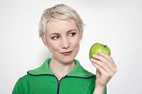 Young woman holding apple, portrait