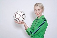 Young woman holding soccer ball, portrait